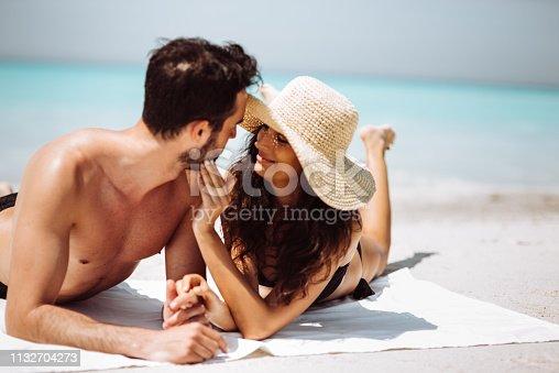 istock couple sunbathing on the beach 1132704273