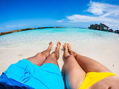 Couple legs sunbathing near the beach during travel holidays vacation outdoors at ocean or nature sea at noon, Maldives. POV.