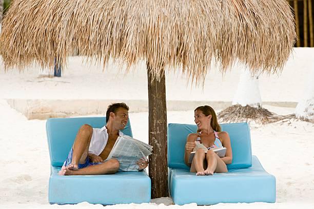 couple sunbathing - newspaper beach stockfoto's en -beelden