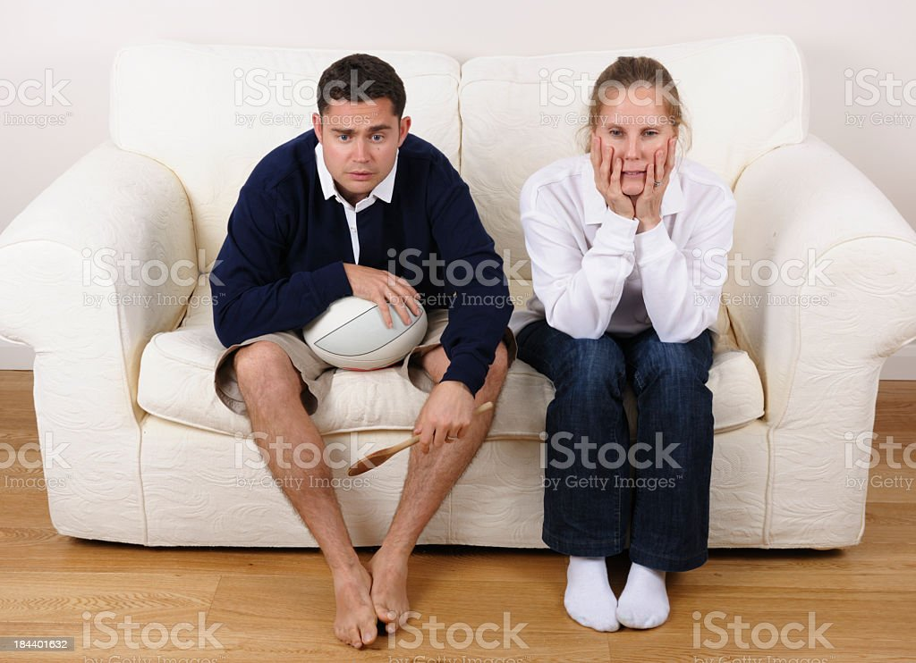 Couple Supporting Rival Rugby Teams Watching A Tense Match Together royalty-free stock photo