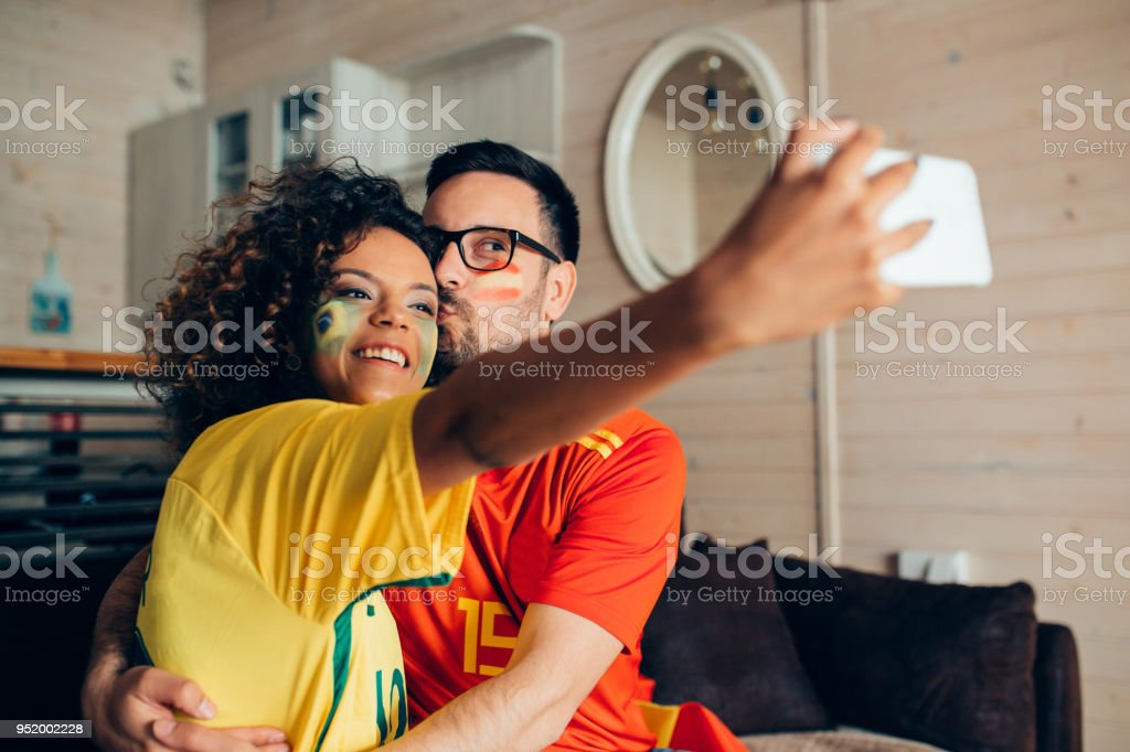 Couple supporting Spanish and Brazilian soccer teams kissing and making a selfie stock photo