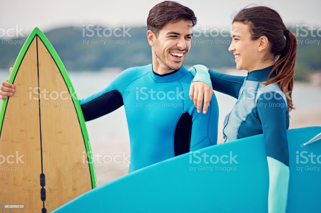 Couple surfers is standing on the beach - Royalty-free Adult Stock Photo