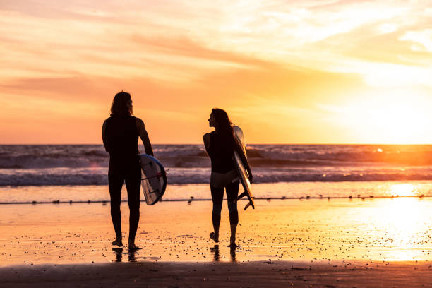 Couple surfing in California Couple surfing in California venice beach stock pictures, royalty-free photos & images