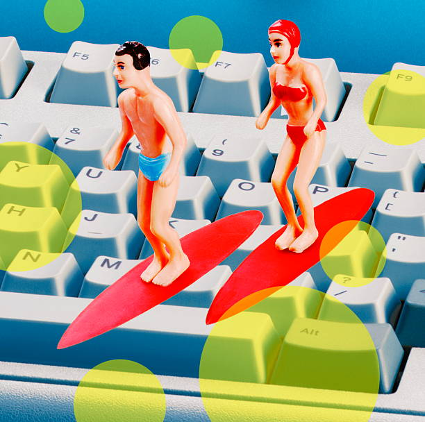 Couple Surfing on Computer Keyboard stock photo