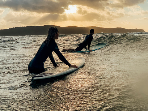 A shot of a young man and woman wearing wetsuits, they are surfing on the sea.