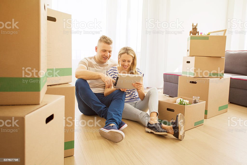 Couple surrounded with moving boxes looking at tablet stock photo