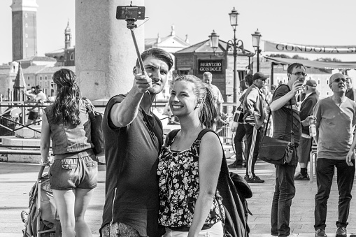 Couple take a selfie in St Mark's bay Venice, Italy