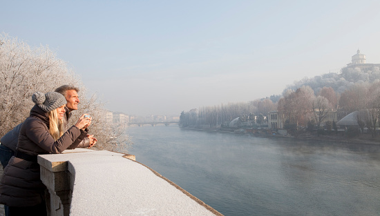 Couple take picture above river, winter, Turin, Piedmont, Italy