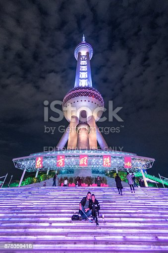 A couple sit on the steps outside The Oriental Pearl tower in Shanghai, taking a selfie with a selfie stick. Other people in the background enter the building.
