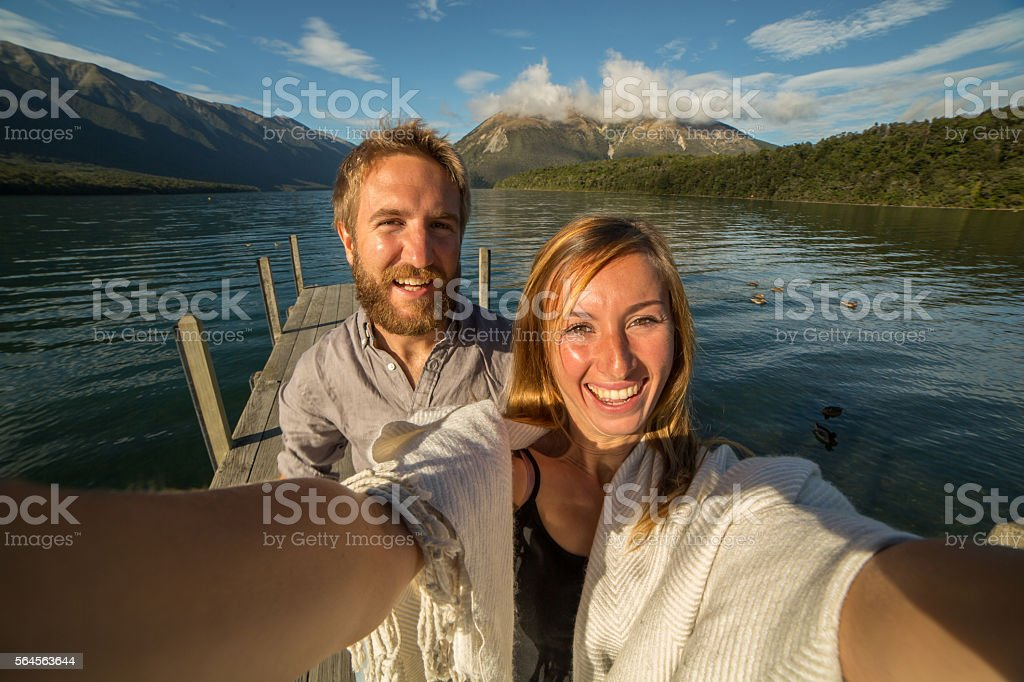 Couple takes selfie portrait on lake pier stock photo