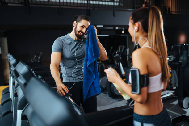 Couple taking a break after workout at gym stock photo