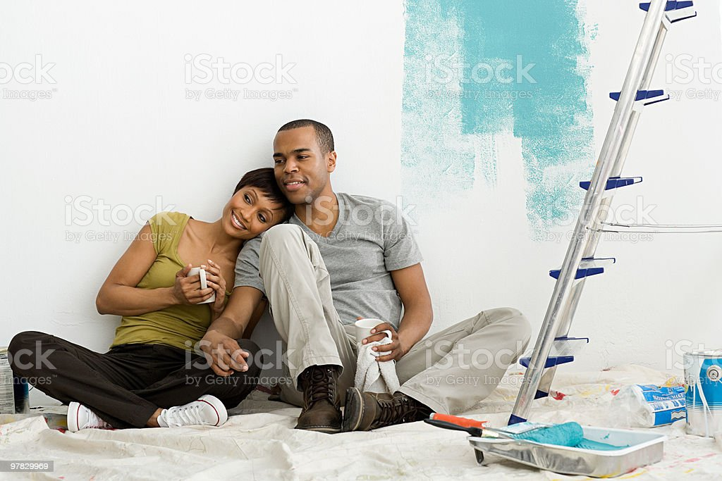 Couple taking a break from painting stock photo