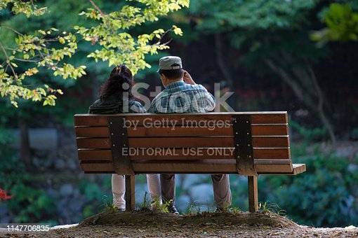 Gochang, Korea - September 19th 2017, Couple taking a break on the bench at Seonunsa Dosolchun. 선운사 도솔천