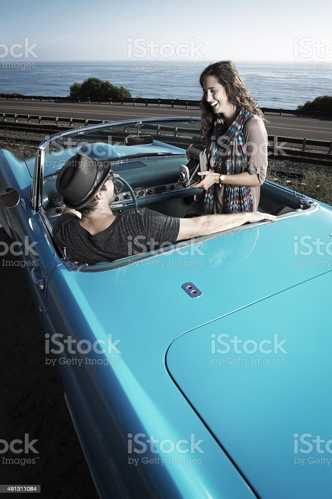 Couple Taking a photo with a Antique camera in a Convertible stock photo