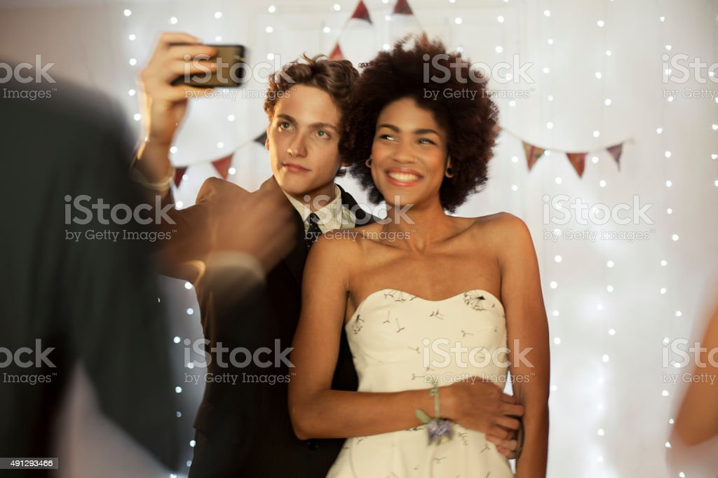 Couple taking a selfie at prom party stock photo