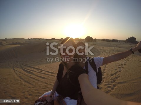 883177796istockphoto Couple taking a selfie in a camel riding in desert 668422178