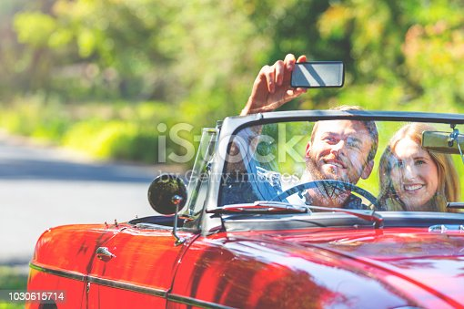 481388538 istock photo Couple taking a selfie in a Convertible Car on the road. 1030615714