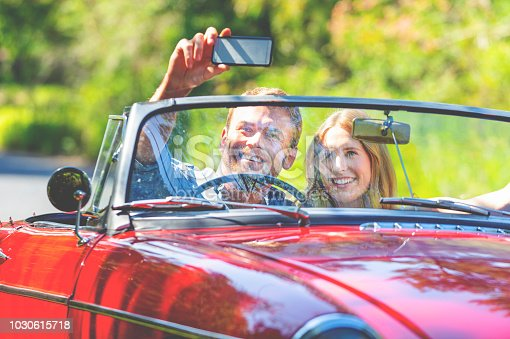 481388538 istock photo Couple taking a selfie in a Convertible Car on the road. 1030615718