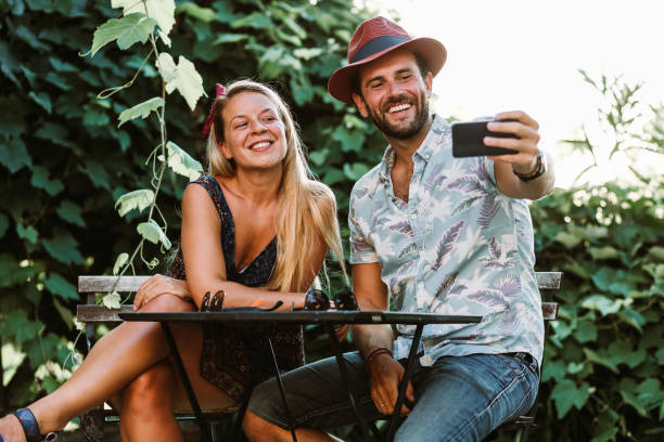 Couple taking a selfie on a terrace in sunset stock photo