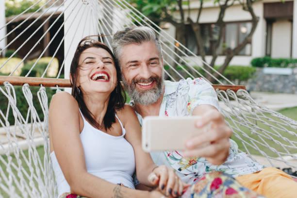 paar nemen een selfie terwijl hij op vakantie - ouder volwassenen koppel stockfoto's en -beelden