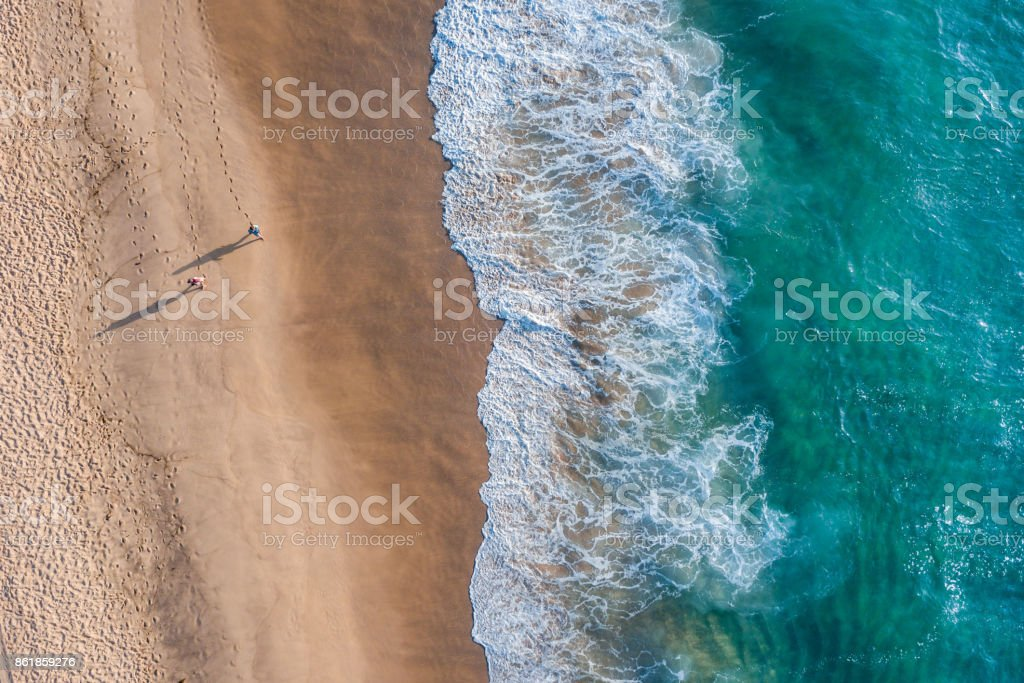 A couple taking a stroll on the beach  - Aerial Photography stock photo