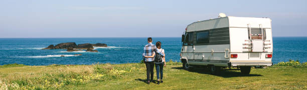 Couple taking a walk near the coast with a camper Young couple taking a walk near the coast with a camper in the background manufactured housing stock pictures, royalty-free photos & images