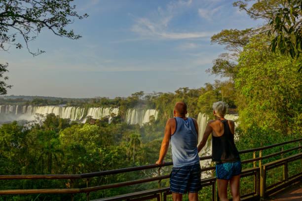 Couple Taking in the Beautiful Iguazu Falls in Iguazu National Park, South America stock photo