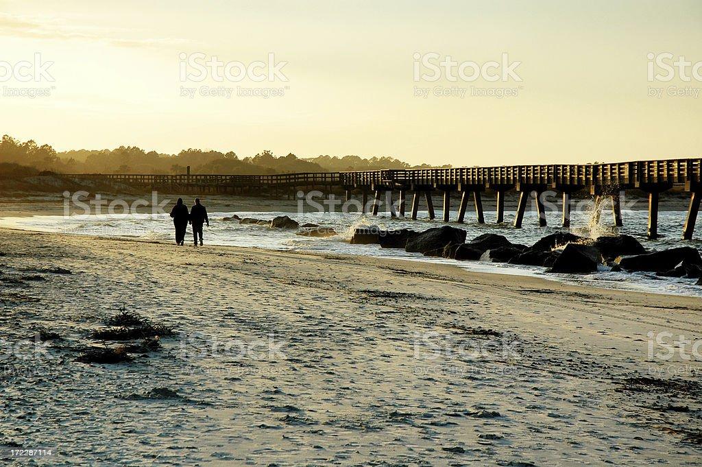 Couple Taking Long Walk On Amelia Island Beach at Sunset stock photo