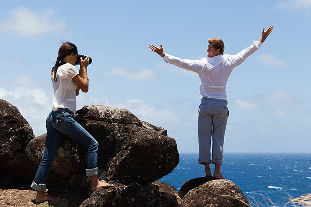 couple taking photo on a cliff with man looking back - carolinemaryan stock pictures, royalty-free photos & images