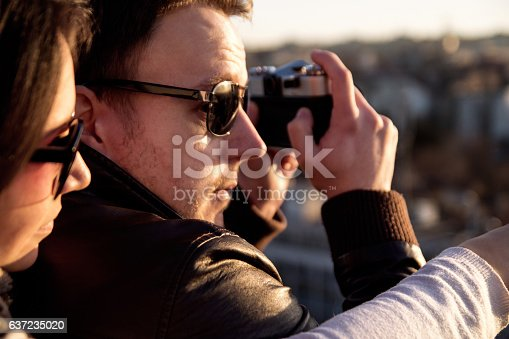 636330566istockphoto Couple taking pictures of sunset on rooftop of the city 637235020