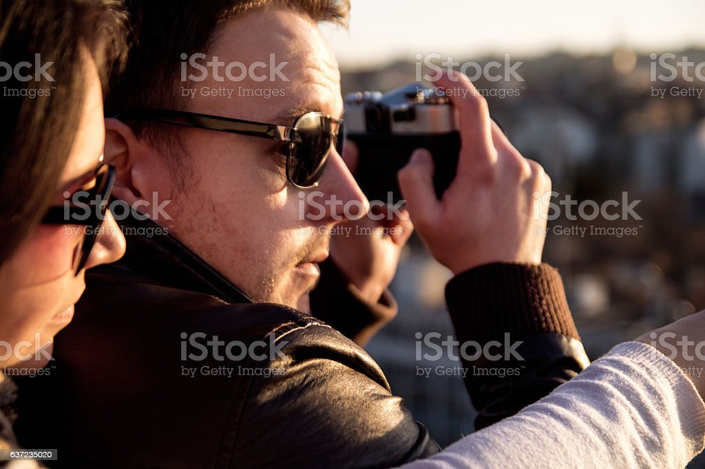 Couple taking pictures of sunset on rooftop of the city stock photo