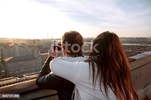 636330566istockphoto Couple taking pictures of the sunset on rooftop of the 640191086