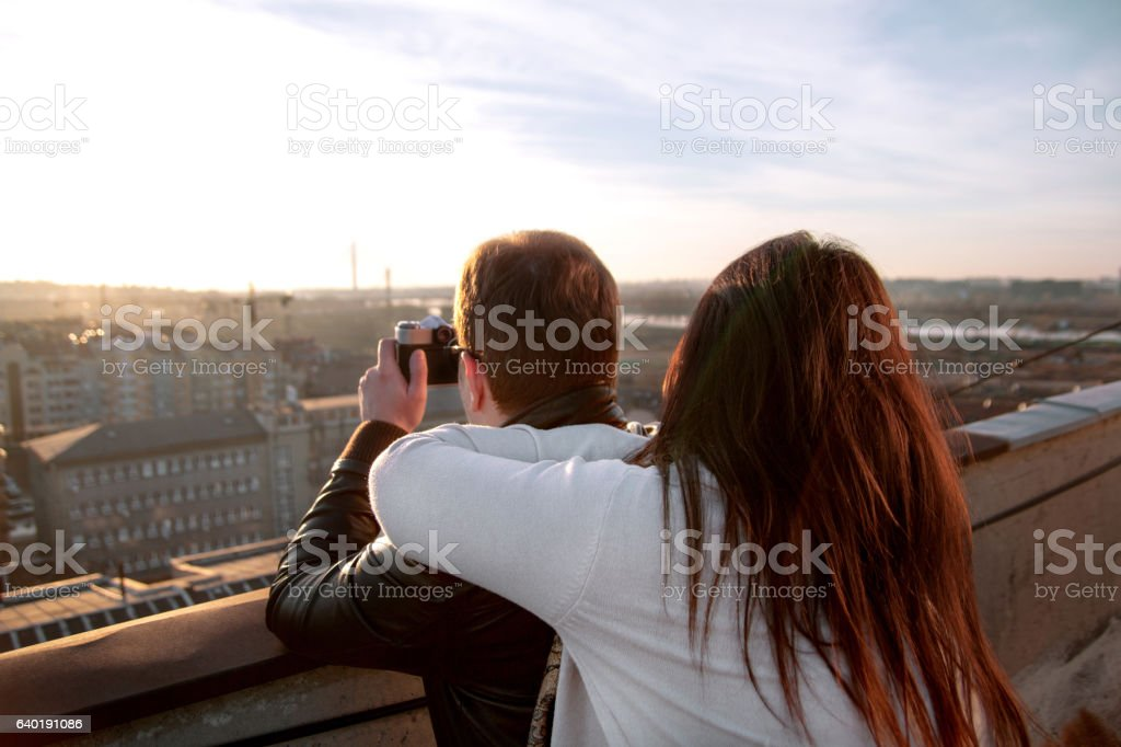 Couple taking pictures of the sunset on rooftop of the - foto de acervo