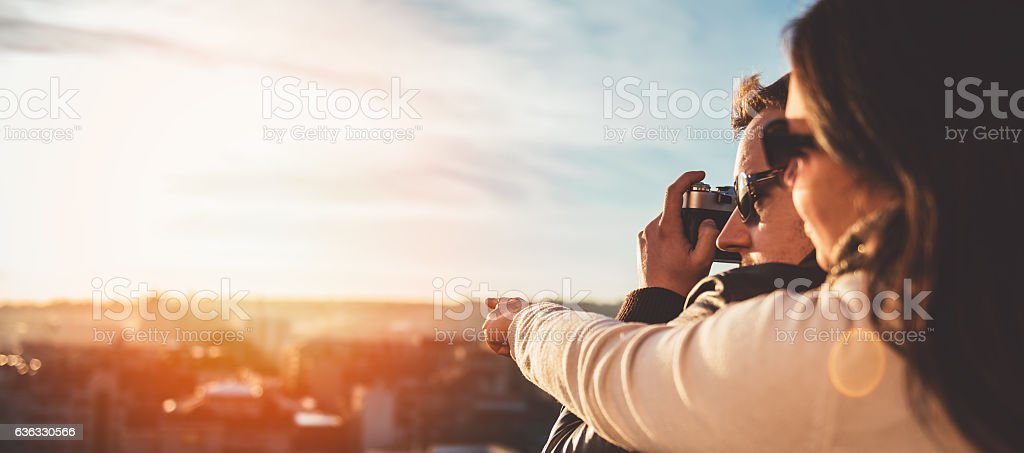 Couple taking pictures on the rooftop stock photo