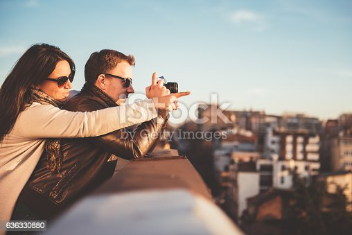 636330566istockphoto Couple taking pictures on the rooftop 636330880
