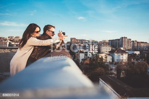 636330566istockphoto Couple taking pictures on the rooftop 636331014