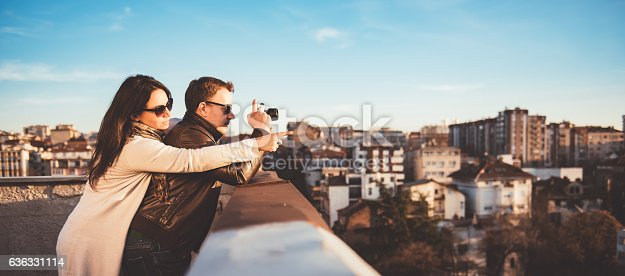 636330566istockphoto Couple taking pictures on the rooftop 636331114