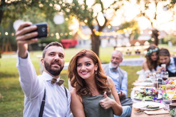A couple taking selfie at the wedding reception outside in the backyard. A couple taking selfie at the wedding reception outside in the backyard. Bride, groom and guests sitting at the table. guest stock pictures, royalty-free photos & images