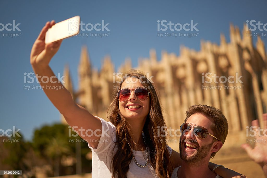 couple taking selfie in front of cathedral stock photo