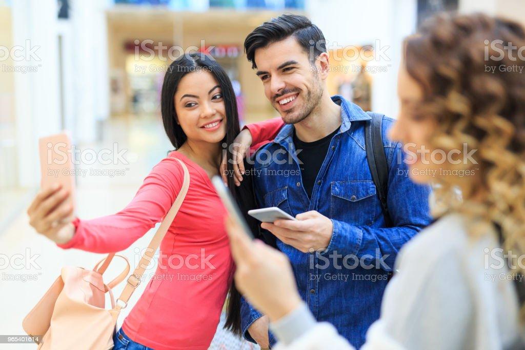Couple taking selfie in shopping mall zbiór zdjęć royalty-free