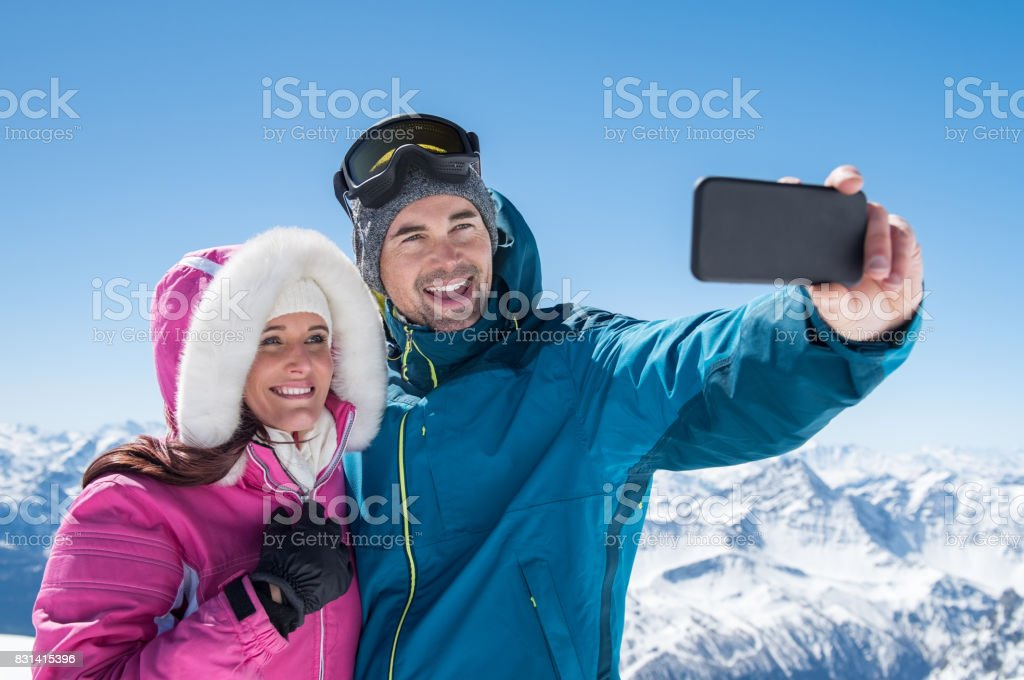 Couple taking selfie in snowy mountain stock photo