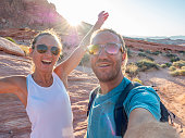 Cheerful young couple taking a selfie portrait with the beautiful landscape of the Valley of fire state park in Nevada, USA\nPeople travel nature communication concept