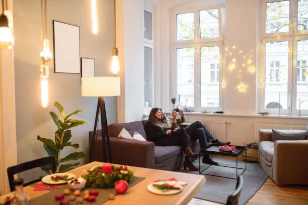 paar nehmen selfie mit smartphone auf sofa zu hause während der weihnachtszeit - partyraum stock-fotos und bilder