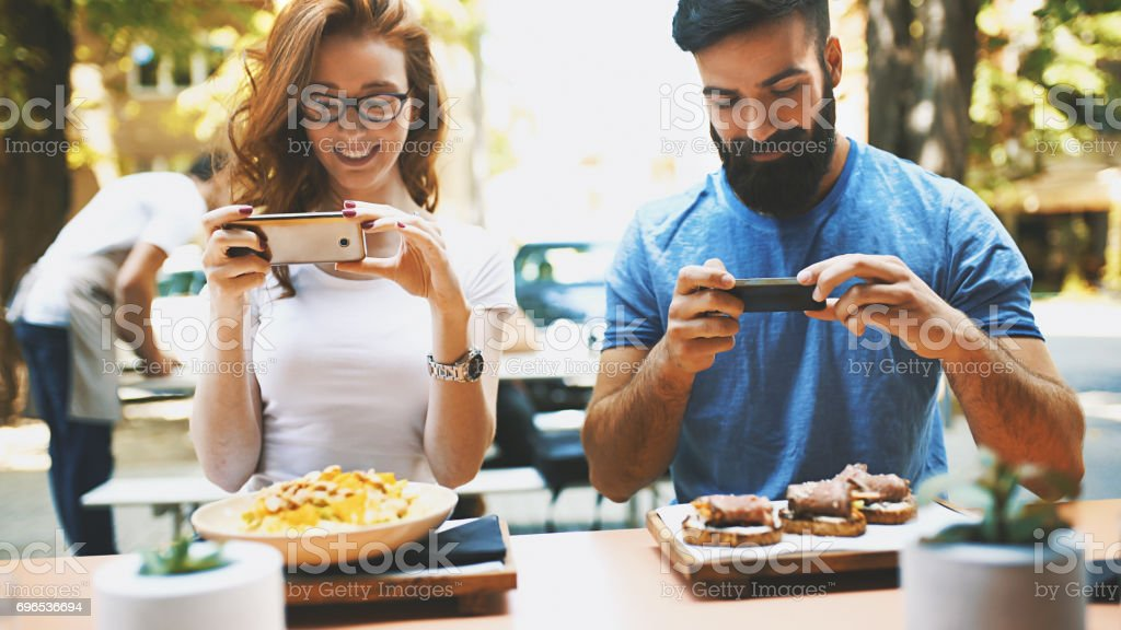 Couple taking shots of food. stock photo
