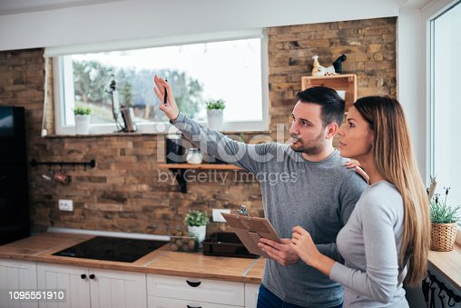 Couple talking about home renovation. Standing in the kitchen and discussing apartment renovation ideas.