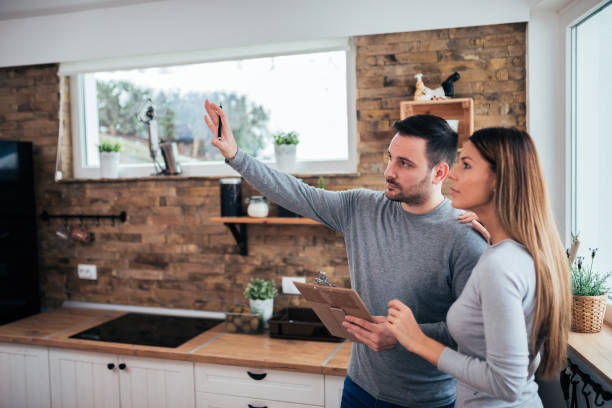 Couple talking about home renovation. Standing in the kitchen and discussing apartment renovation ideas. stock photo