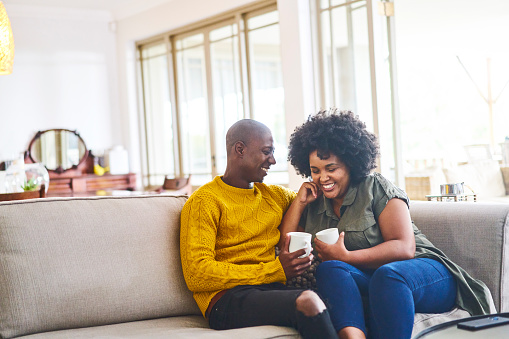 Couple talking and laughing together over coffee at home
