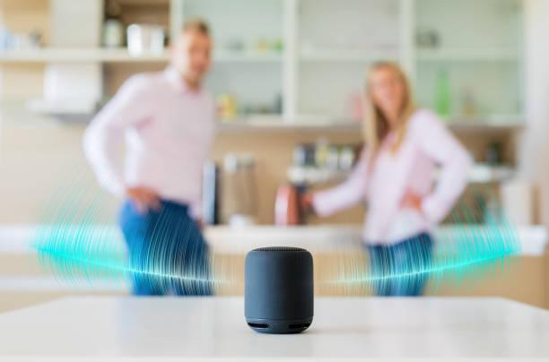 Casal conversando e ouvindo o orador inteligente em casa - foto de acervo