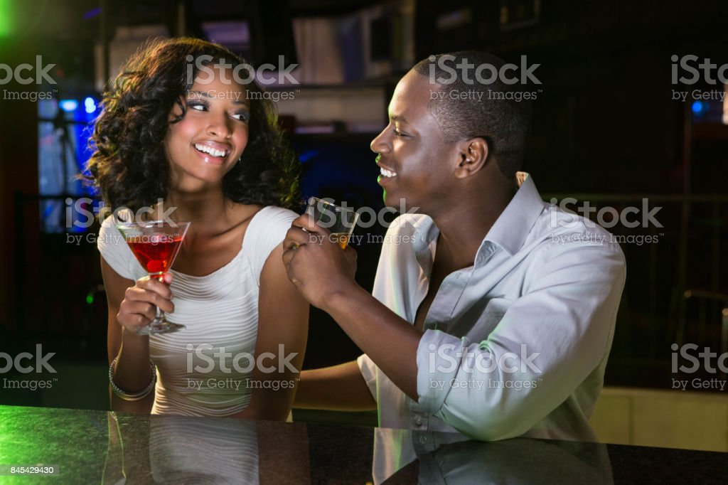Couple talking and smiling while having drinks at bar counter stock photo