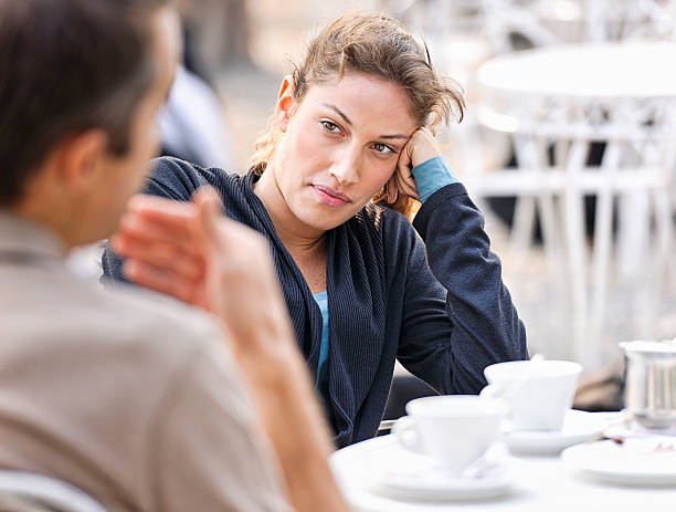 Couple Talking at a Cafe A woman listening to a man (defocussed) talking during a discussion at an outdoor cafe. prettige verrassingen stock pictures, royalty-free photos & images